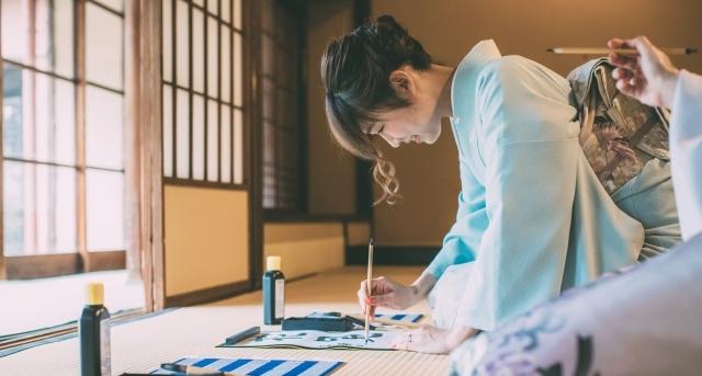 着物を着た女性が習字をしているイメージ画像